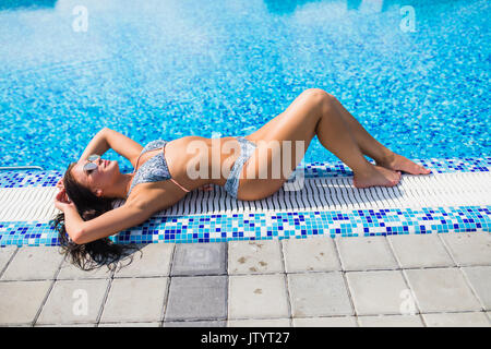 Overhead view of a beautiful female fashion model wearing red bikini resting on the edge of a pool at a luxury resort. - Stock Photo
