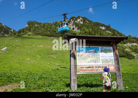 Woman walker reading information panel as Hochalmbahn cable car cabin is coming down the mountain, Hochalm, Kreuzeck, - Stock Photo