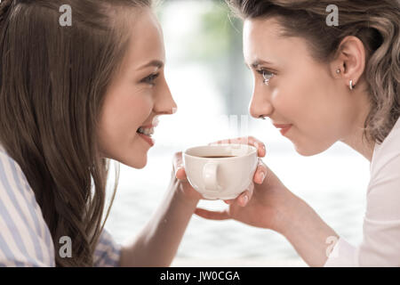 young smiling girlfriends drinking coffee and looking at each other - Stock Photo