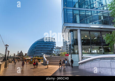 Queens Walk at southwark banks with people and view of the modern building of city hall and office buildings on - Stock Photo