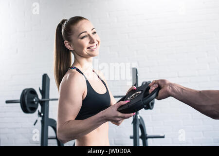 Cropped shot of man giving weight for dumbbell to smiling muscular woman - Stock Photo