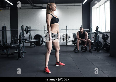 woman doing strength training with barbell while man sitting at gym - Stock Photo