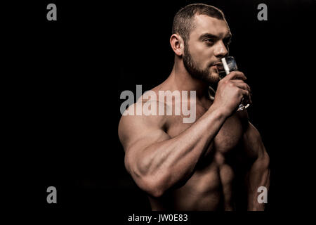 side view of shirtless man drinking water and looking away isolated on black - Stock Photo
