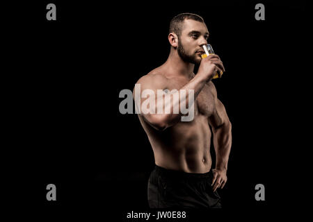 side view of sportive shirtless man drinking juice isolated on black - Stock Photo