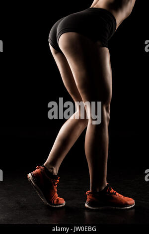 Cropped shot of muscular young sportswoman in shorts and sneakers standing isolated on black  - Stock Photo