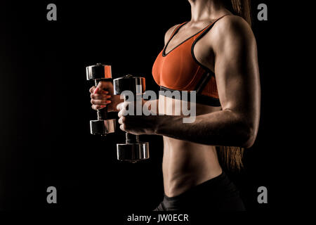 Cropped shot of muscular young sportswoman exercising with dumbbells isolated on black - Stock Photo