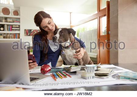 Female interior designer petting dog at desk in home office - Stock Photo