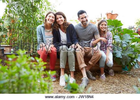 Portrait smiling Latina family in vegetable garden - Stock Photo