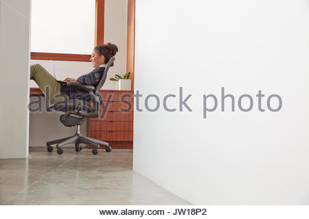 Businesswoman using laptop with feet up in home office - Stock Photo