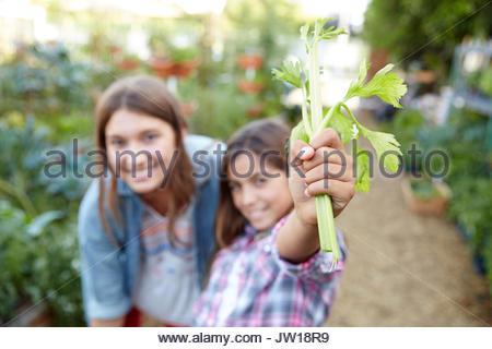 Portrait smiling Latina sisters holding fresh celery stalk in garden - Stock Photo