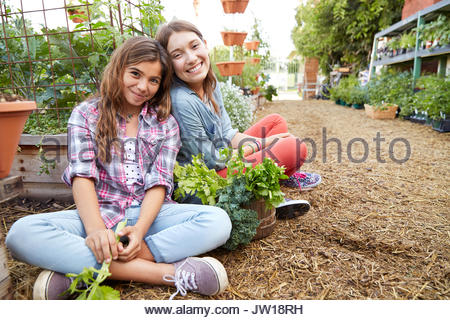 Portrait Latina sisters harvesting vegetables in garden - Stock Photo
