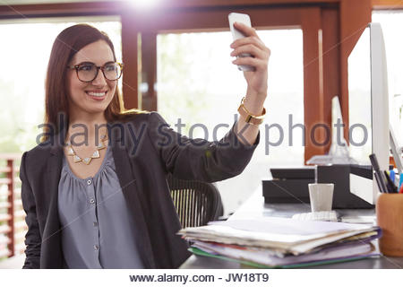 Smiling businesswoman taking selfie with camera phone in office - Stock Photo