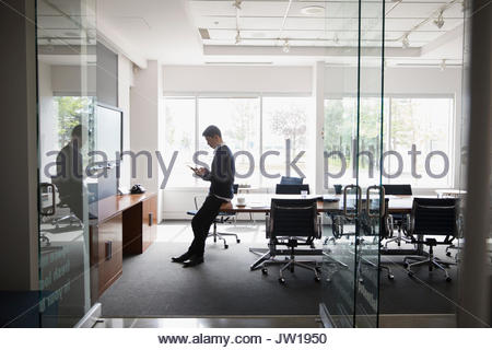 Businessman using digital tablet in conference room - Stock Photo