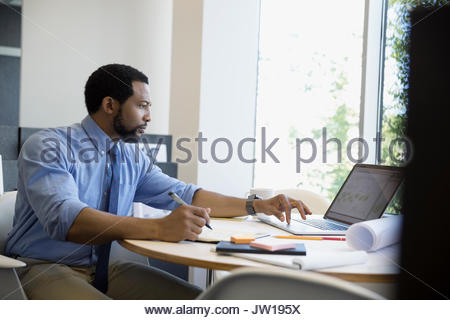 Male architect using laptop and taking notes in office - Stock Photo