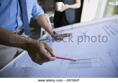 Male architect reviewing blueprints in office - Stock Photo