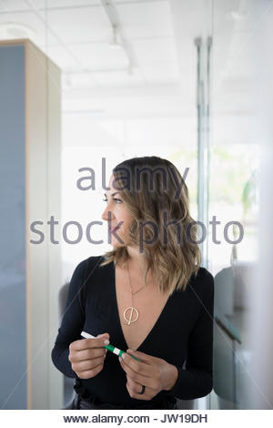 Pensive businesswoman looking away at whiteboard - Stock Photo