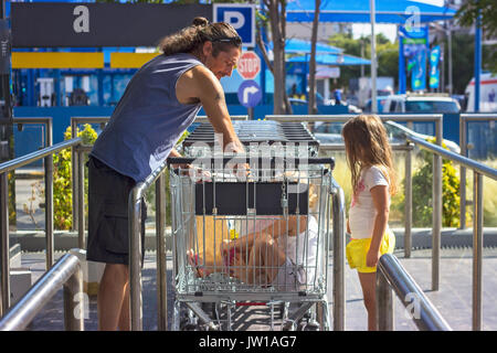 Man with two kids packing groceries from shopping cart in front of supermarket - Stock Photo