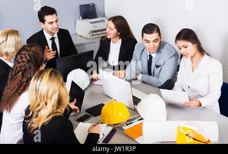 Team of positive professionals discussing business project and smiling in office. Focus on right man - Stock Photo
