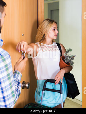 Frustrated young man and sad wife standing at doorway with luggage - Stock Photo