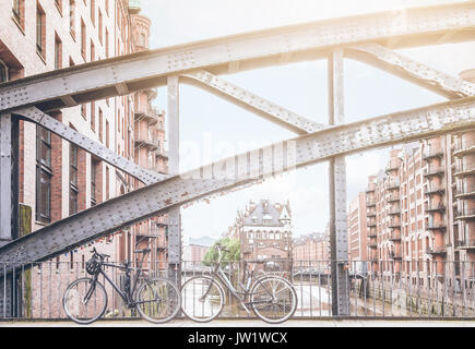 bicycles parked against iron handrail on a bridge in the old warehouse district Speicherstadt in Hamburg, Germany - Stock Photo