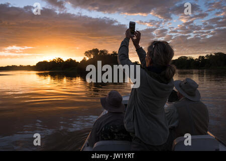 Tourist photographing the sunset with an iPhone - Stock Photo