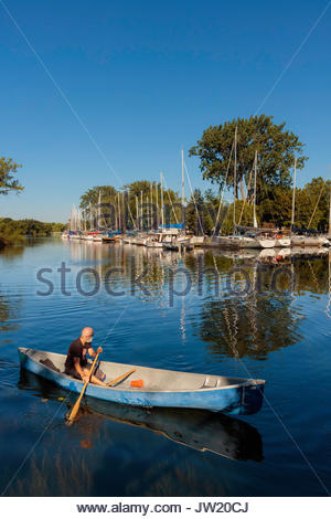 canoe canoeing Toronto Islands Park lagoon trees reflected Toronto Ontario Canada - Stock Photo
