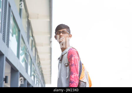 portrait of male indian high school student with schoolbag - Stock Photo