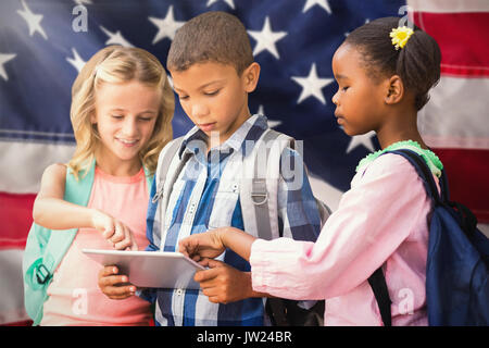 Students using digital tablet  against close-up of red and white american flag - Stock Photo