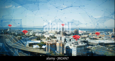 Red wifi symbol against cityscape against sky - Stock Photo