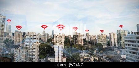 Red wifi symbol against city against blue sky - Stock Photo