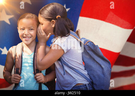 Girl with backpack whispering in friend ear against american flag with stripes and stars - Stock Photo