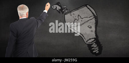 Rear view of serious businessman standing and writing against black wall - Stock Photo
