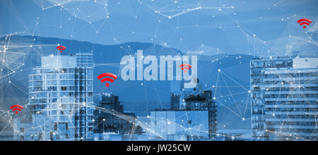 Red wifi symbol against buildings in city against blue sky - Stock Photo