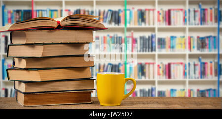 Stack of books by yellow mug on wooden table against multi colored bookshelf in library - Stock Photo