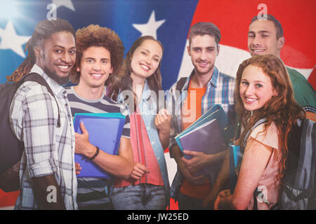 Smiling group of students holding folders against american flag with stripes and stars - Stock Photo