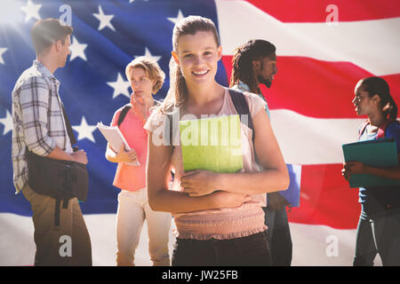 Happy students outside on campus  against close-up of us flag - Stock Photo