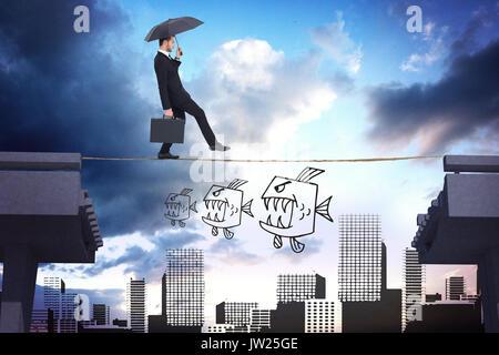Businessman holding briefcase under umbrella against bridge over city - Stock Photo