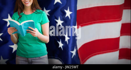 Student picking a book from shelf in library against flag with stripes and stars - Stock Photo