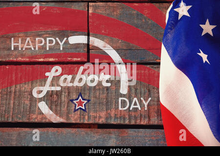 Digitally generated image of happy labor day banner against american flag on a wooden table - Stock Photo