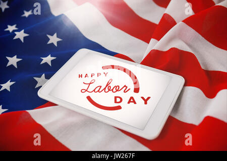 A white flash with a black blackground against tablet computer on crumbled american flag - Stock Photo