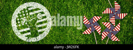 Cropped hand holding tool and american flag on red poster against full frame shot of grassy field - Stock Photo