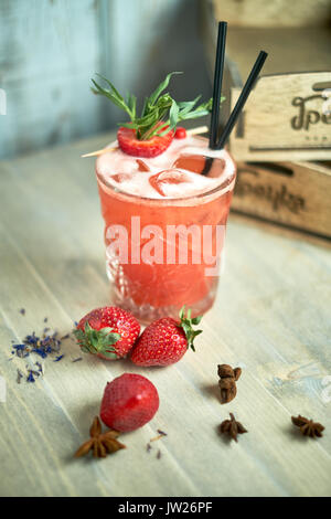 Strawberry lemonade with lime and ice in mason jar on a wooden table jpg - Stock Photo