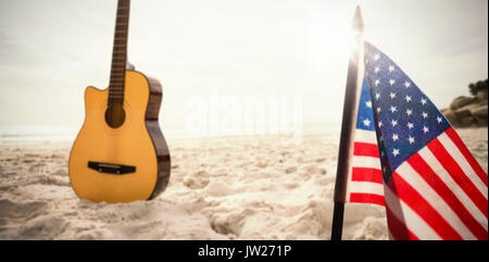 A white flash with a black blackground against acoustic guitar in sand - Stock Photo