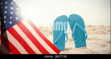 A white flash with a black blackground against blue flip flop in sand - Stock Photo