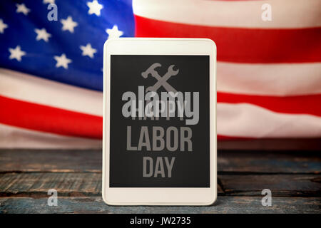 A white flash with a black blackground against digital tablet on table against american flag - Stock Photo