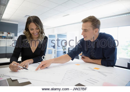 Architects discussing, reviewing blueprints at table in open plan office - Stock Photo