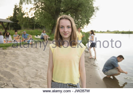Portrait smiling pre-adolescent girl on summer lakeside beach - Stock Photo