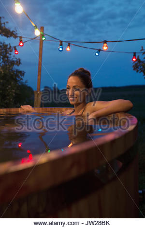 Smiling young woman relaxing, soaking in hot tub under string lights on night patio - Stock Photo