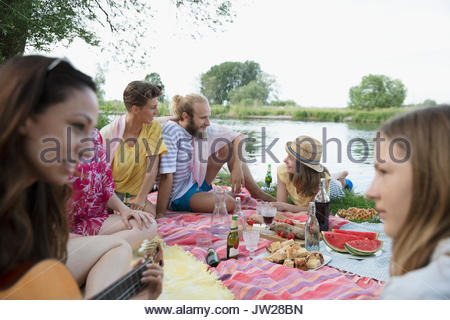 Friends and family relaxing, enjoying summer picnic at lakeside - Stock Photo