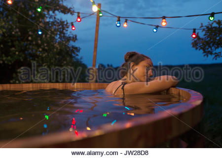 Serene young woman relaxing, soaking in hot tub under string lights on night patio - Stock Photo